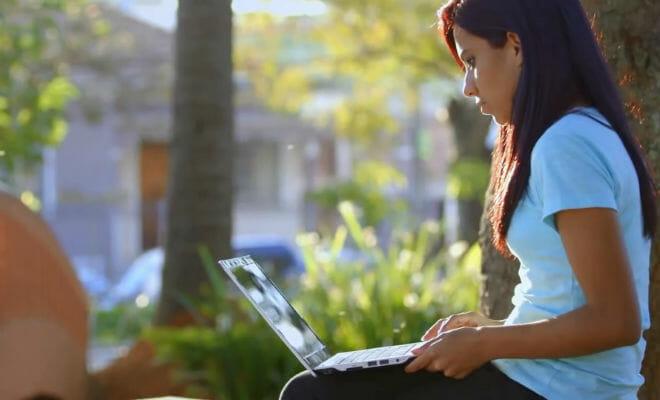 jovem usando notebook em praça