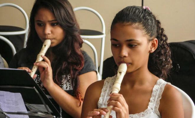 adolescentes tocando flauta doce